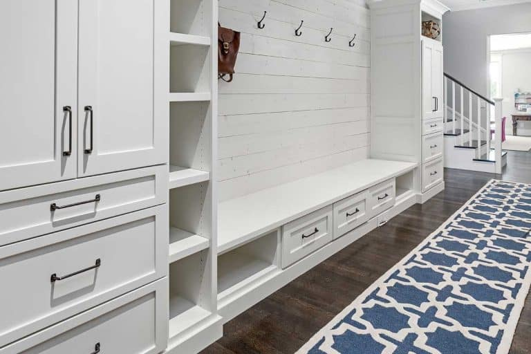 Mud room of a white modern house with hardwood floor and white wooden cabinets, What Is The Mudroom In A House?