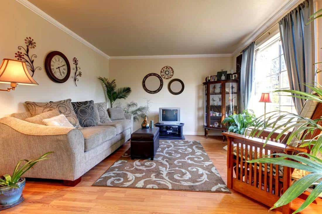 Old fashioned living room with circular mirrors and clocks with gray couch