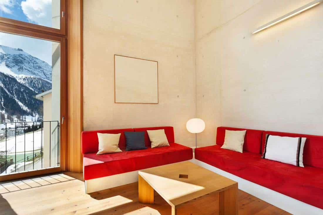 Red couches inside small living room with wooden framed window