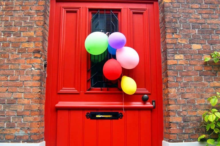 Red entrance door of a brick wall residential house with various colored birthday party balloons, How to Decorate a Door for a Birthday Party?