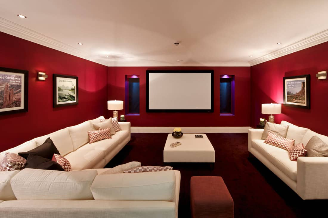 Red velvet colored wall with pictures hanged colored with a dirty white couch