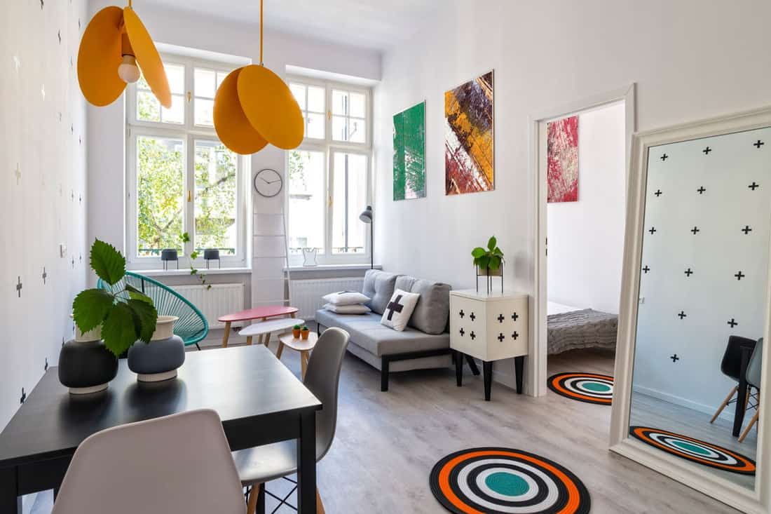 Scandinavian themed living room with yellow colored lamps and white walls with paintings