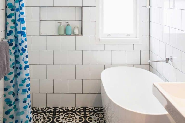 Small bathroom design with white tile walls, integrated shower and bath area