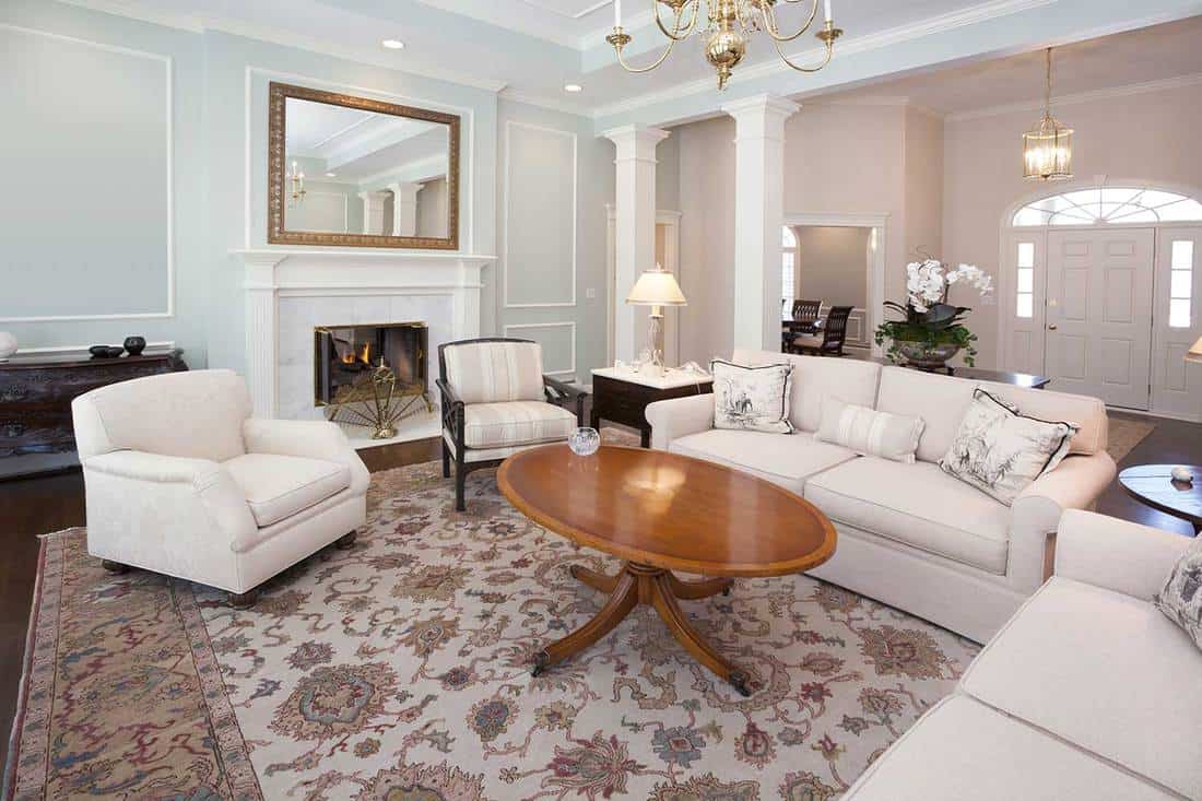 Spacious living room with marble fireplace, wooden coffee table and white sofa set