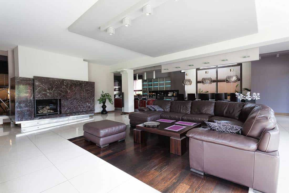 Spacious modern living room with huge leather sofa, coffee table and fireplace