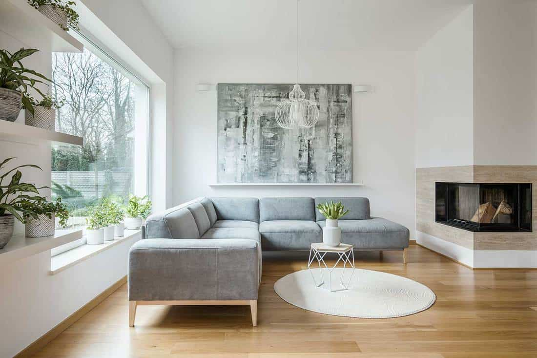 Spacious white living room interior with gray corner couch, big modern art painting and fireplace