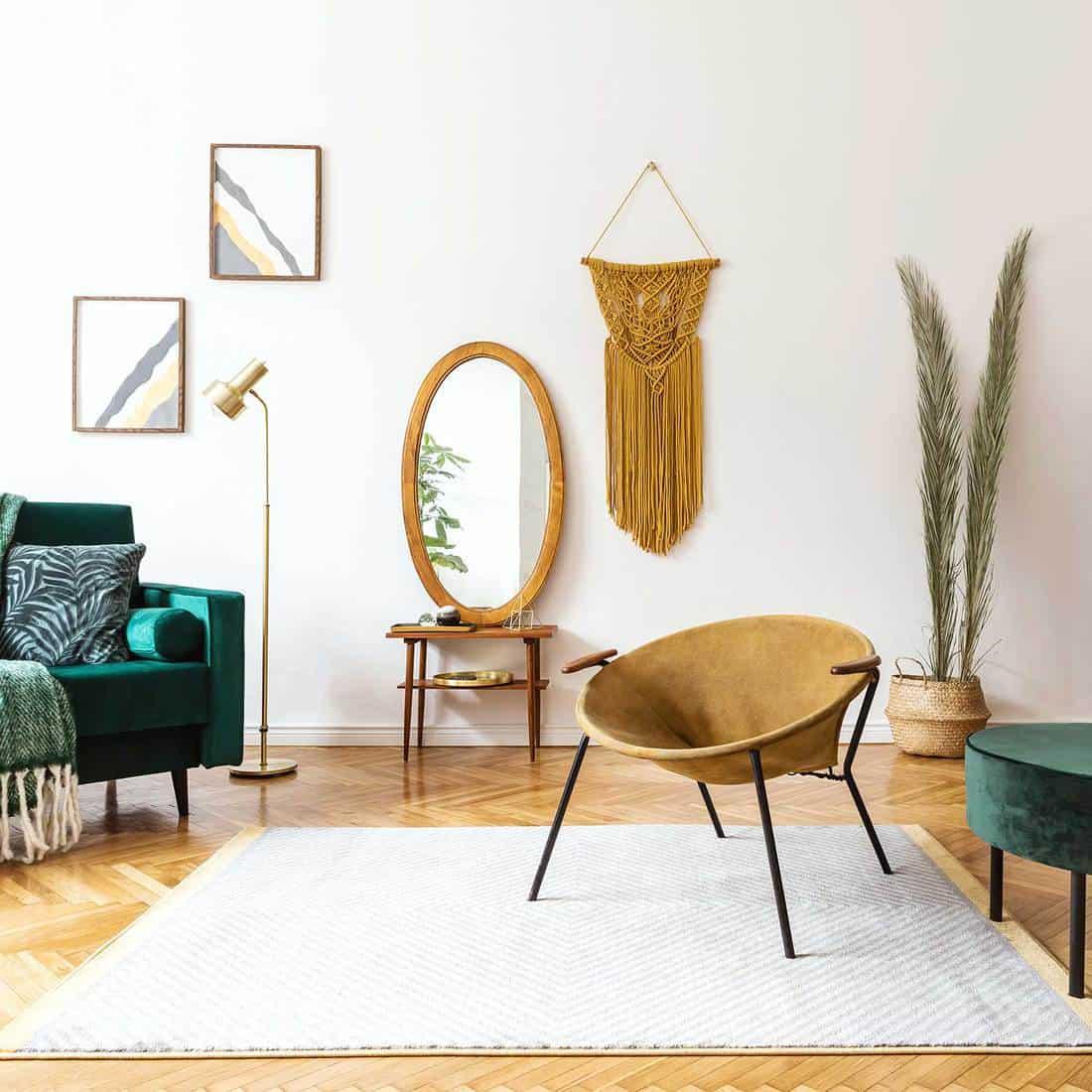 Stylish and elegant interior of living room with design gold armchair, velvet sofa, lamp, poster frames