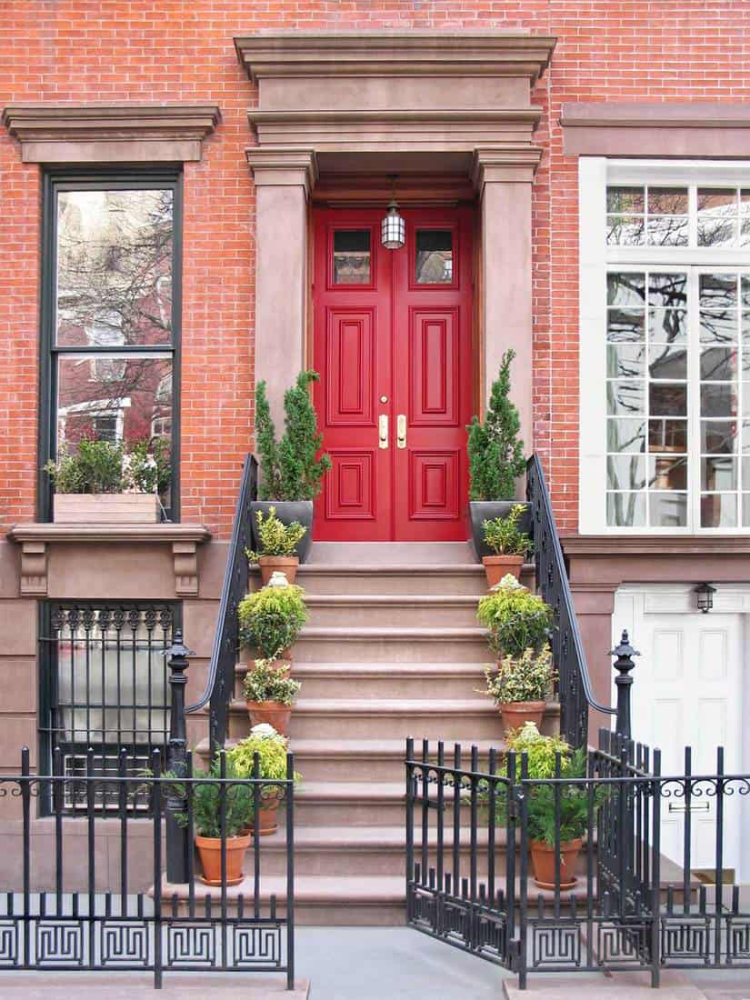 Townhouse red double door entrance with ornate railings and gate