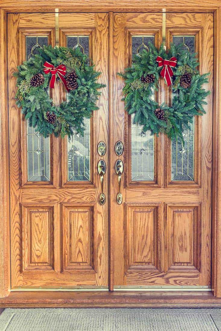 Two Christmas wreaths hanging from an elegant brown double front door