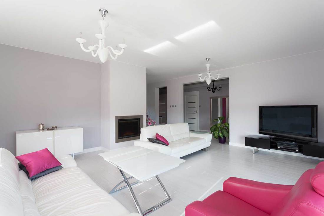 Vibrant cottage living room with fireplace, huge tv, cozy sofa, white table and pink armchair