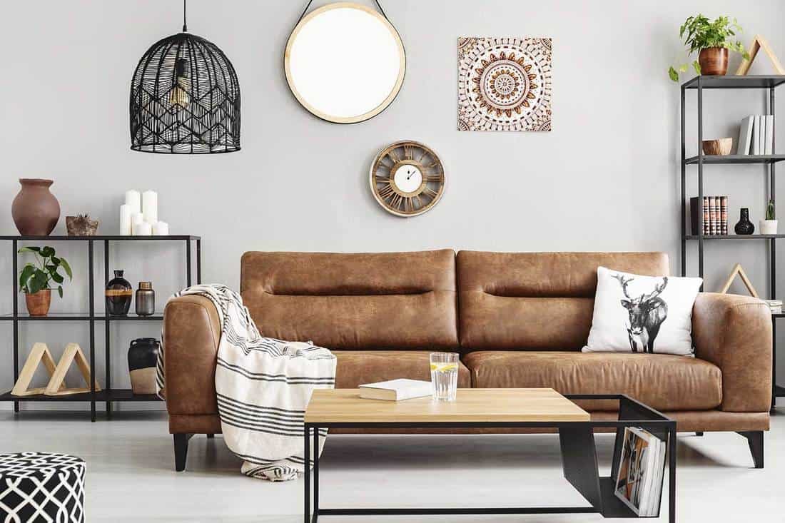 Warm ethno living room with big comfortable leather couch and metal furniture