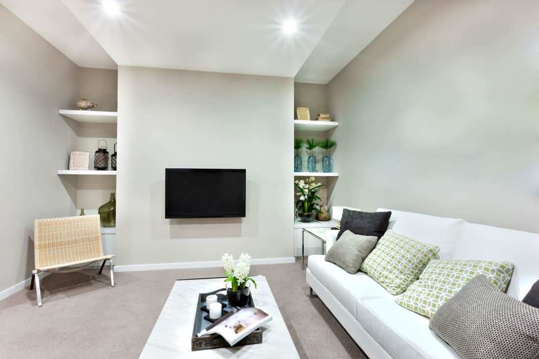 White couch inside small living room and TV mounted at wall