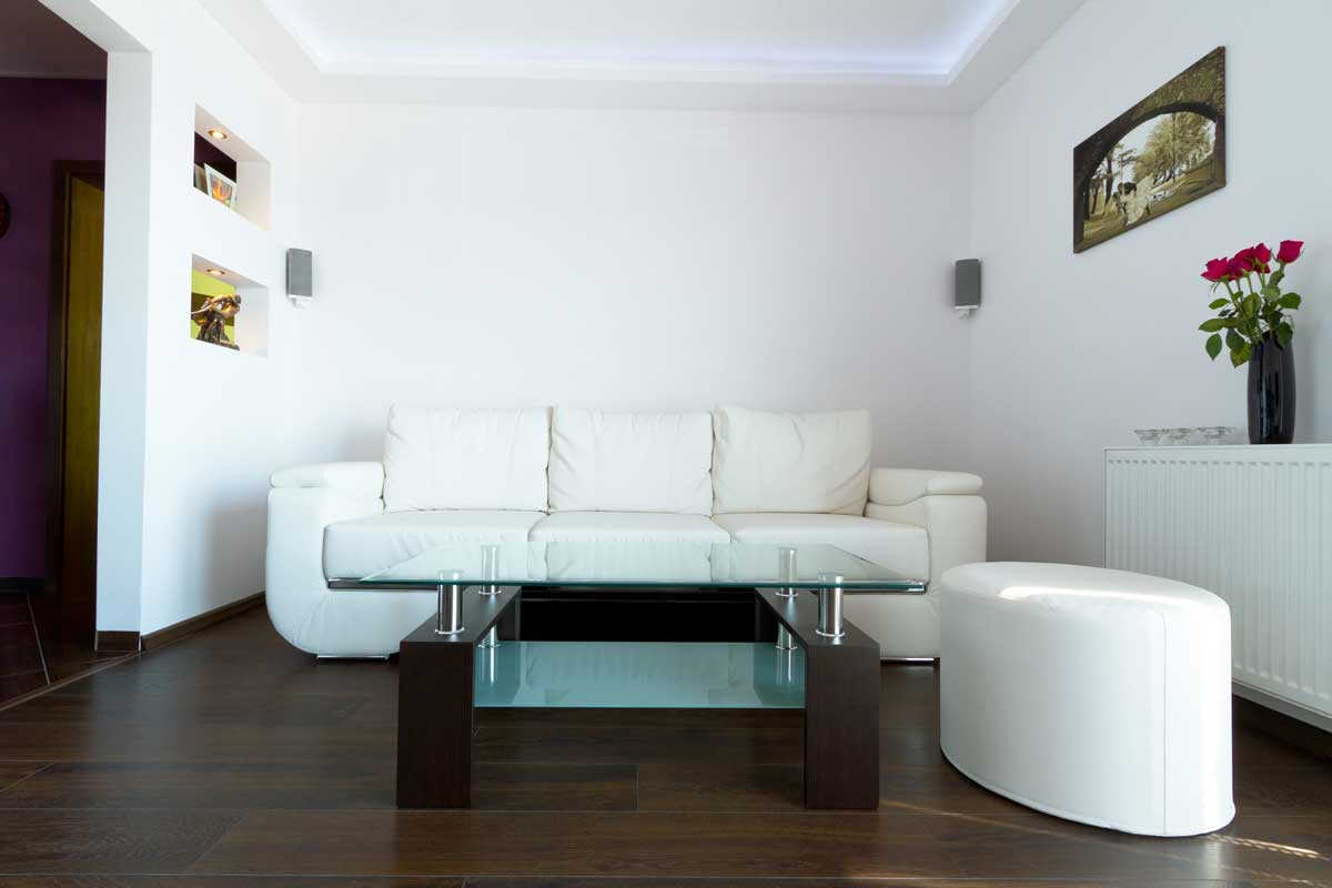 White modern living room with dark wooden panel flooring and white couches