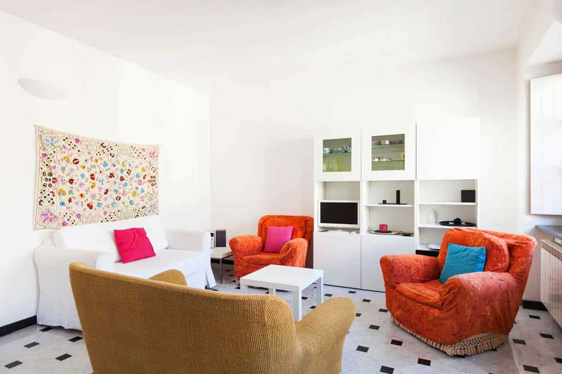 White wall living room with colorful furniture and dotted flooring