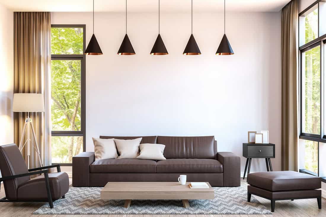 White wall living room with cone shaped hanging lamps and brown sofa