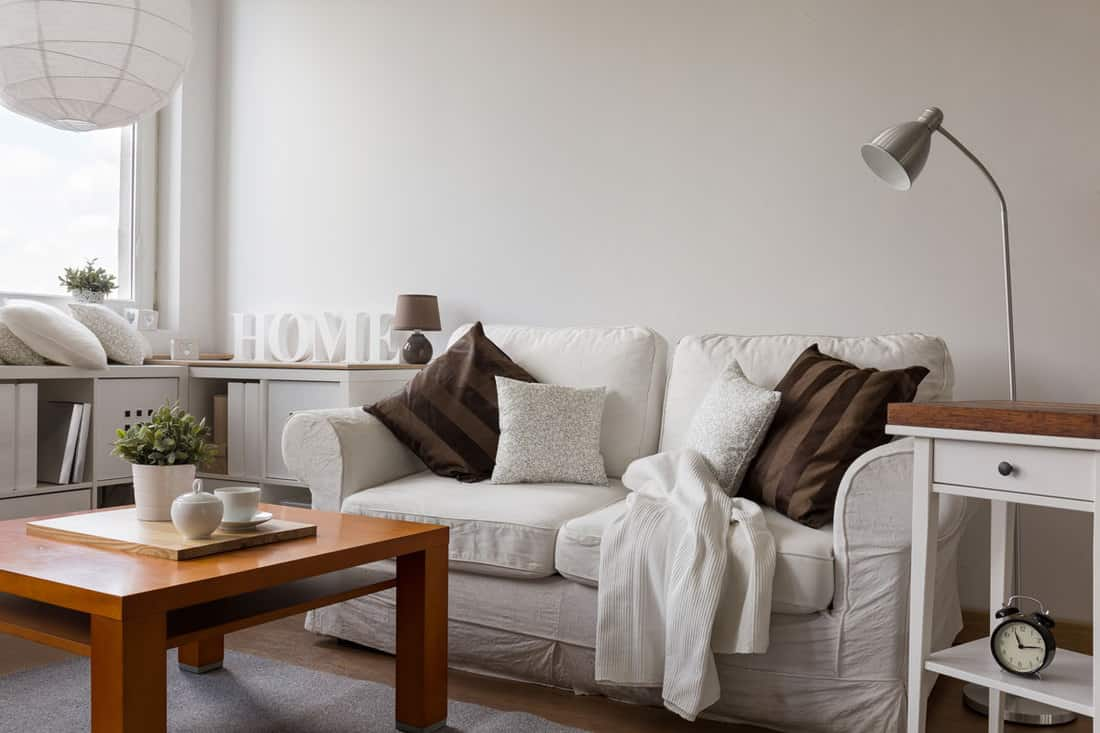 Wooden table and white couch with brown pillows inside small living room