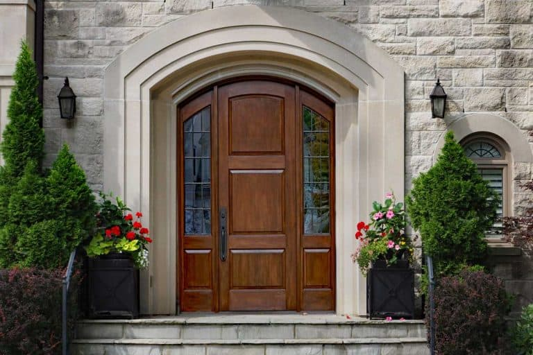 elegant front door of stone house with flagstone steps, How Much Does A Front Door Cost?