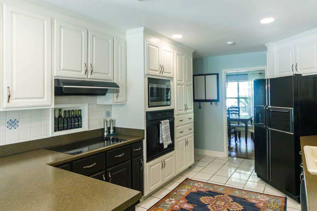 Small kitchen with white cabinets and a tiled floor