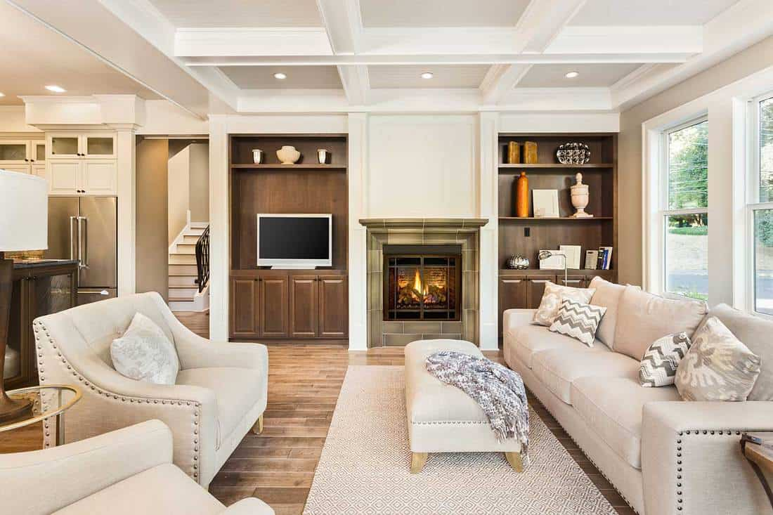 Beautiful living room with hardwood floors, coffered ceiling, and fireplace in new luxury home