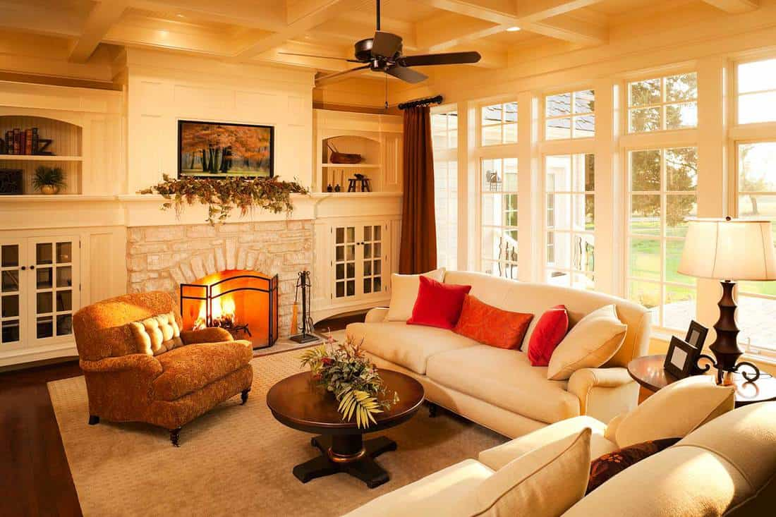 Elegant home living room with a stone fireplace and large windows looking out into the yard