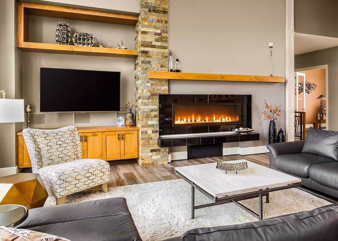 Furnished living room in a luxury home with modern fireplace, black leather sofa, TV and accent chair