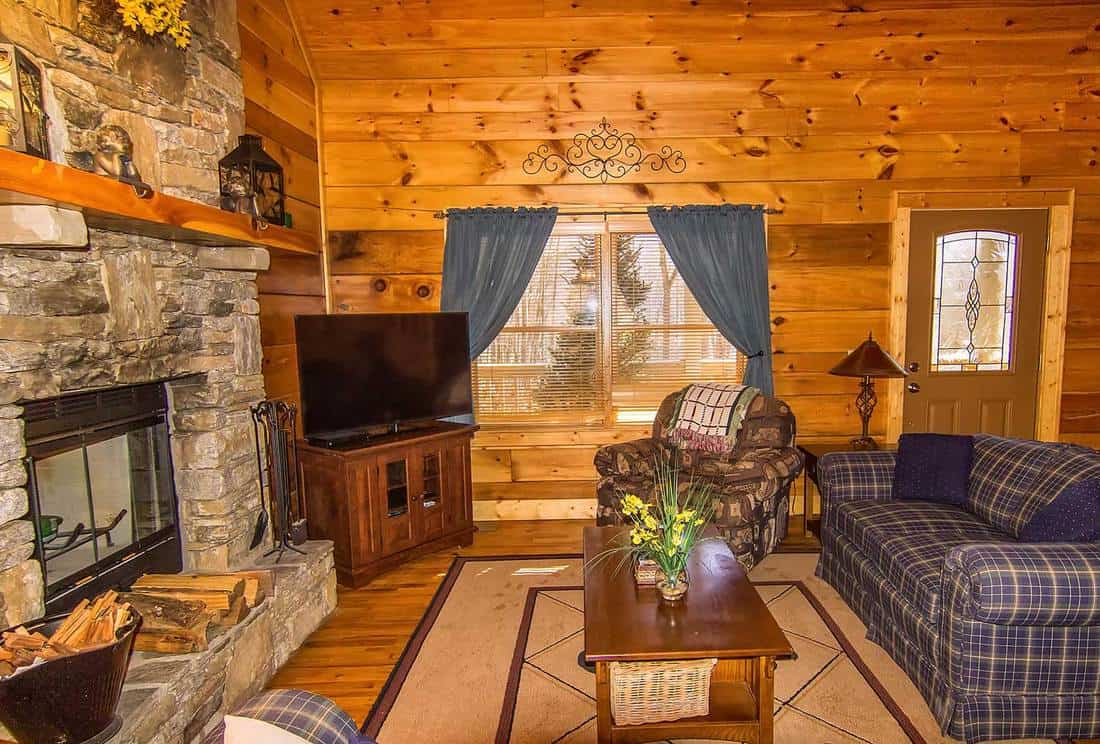 Interior of a log cabin living room with stone fireplace and seating area