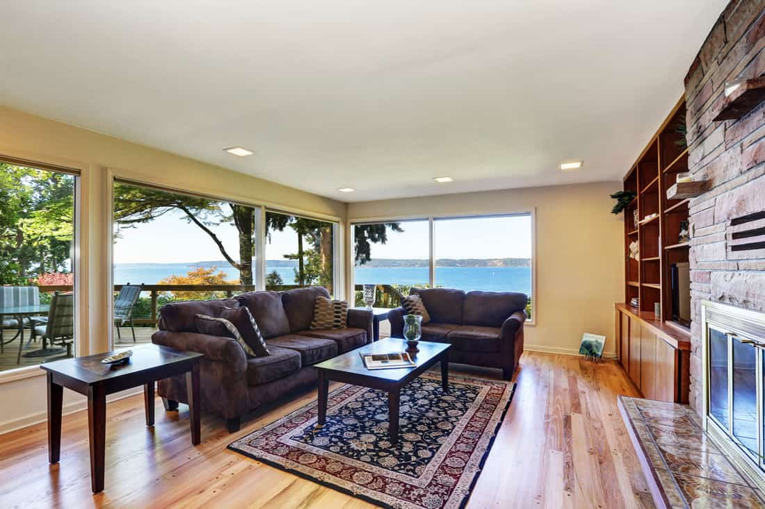 Interior of nicely furnished living room with large windows overlooking back deck. Hardwood floor, brown chocolate sofas, Persian style rug, natural stone wall trim and a fireplace.