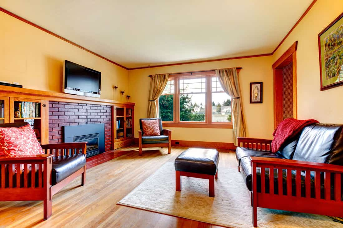 Ivory bright elegant living room with hardwood floor. Furnished with leather couch, chairs, brick background fireplace