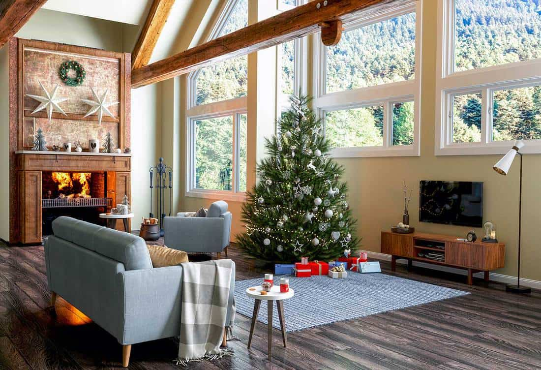 Large christmas decorated living room with TV, fireplace and glass windows