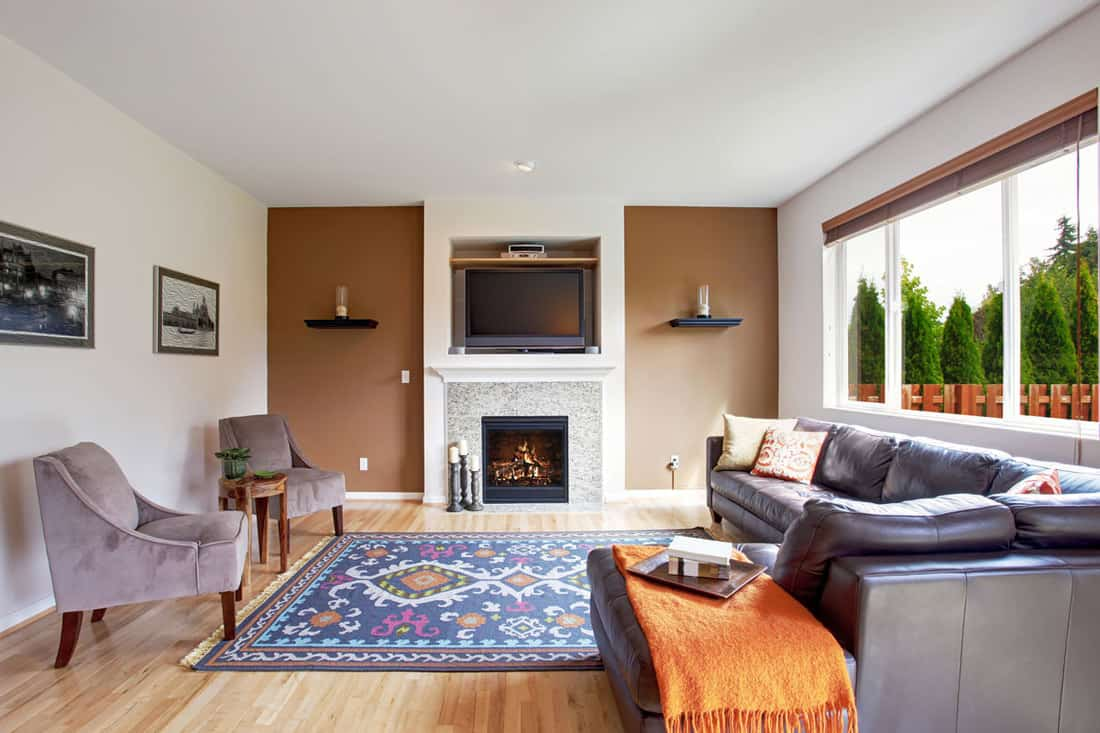 Light brown tone living room with fireplace and tv. Comfort leather couch with pillows and orange blanket