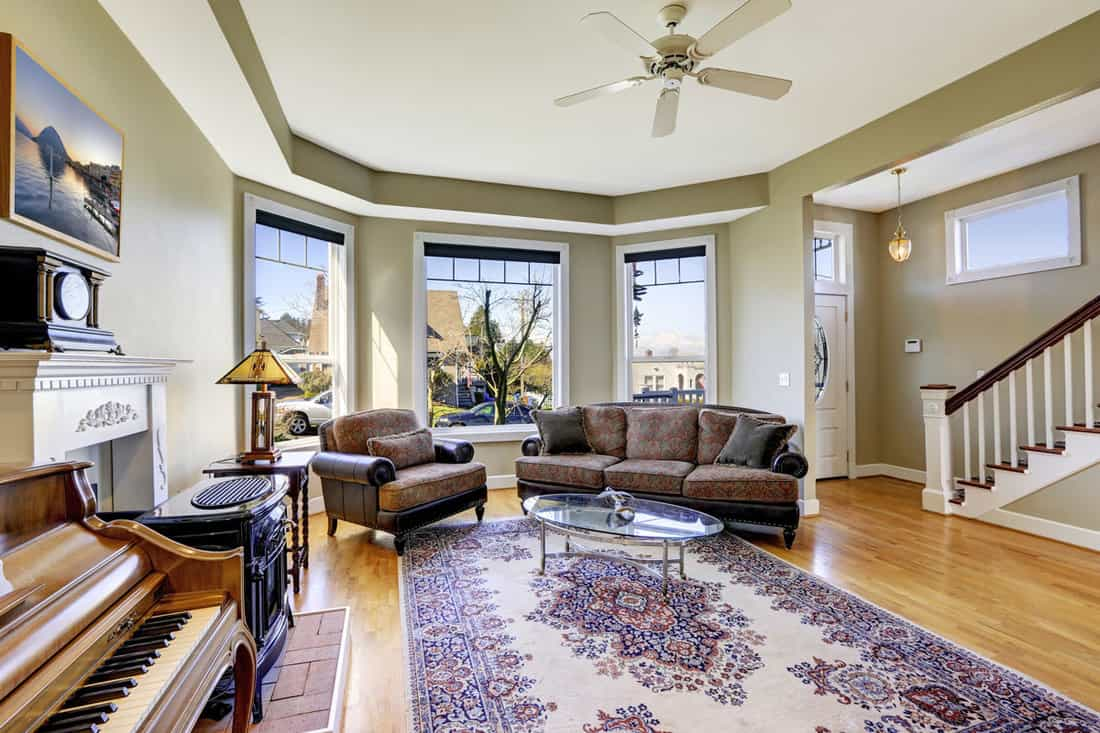 Living room with antique sofa, long patterned rug, chair, coffee table and piano