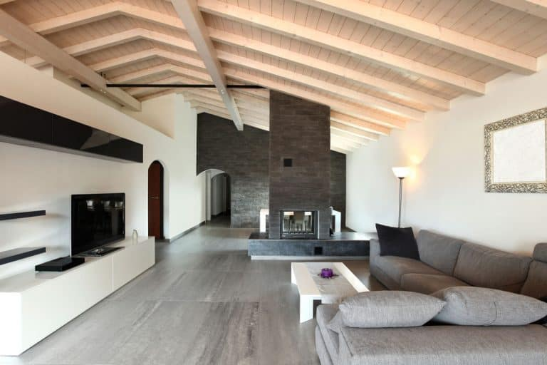 Living room with protruding trusses and center chimney with gray sofa, 55 Huge Living Room Ideas [Picture Inspiration]