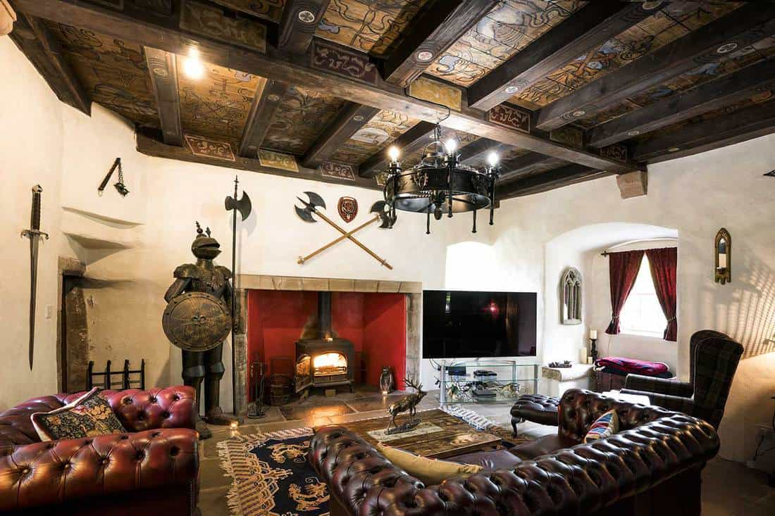 Medieval style living room with knight in armor, weapons and leather furniture