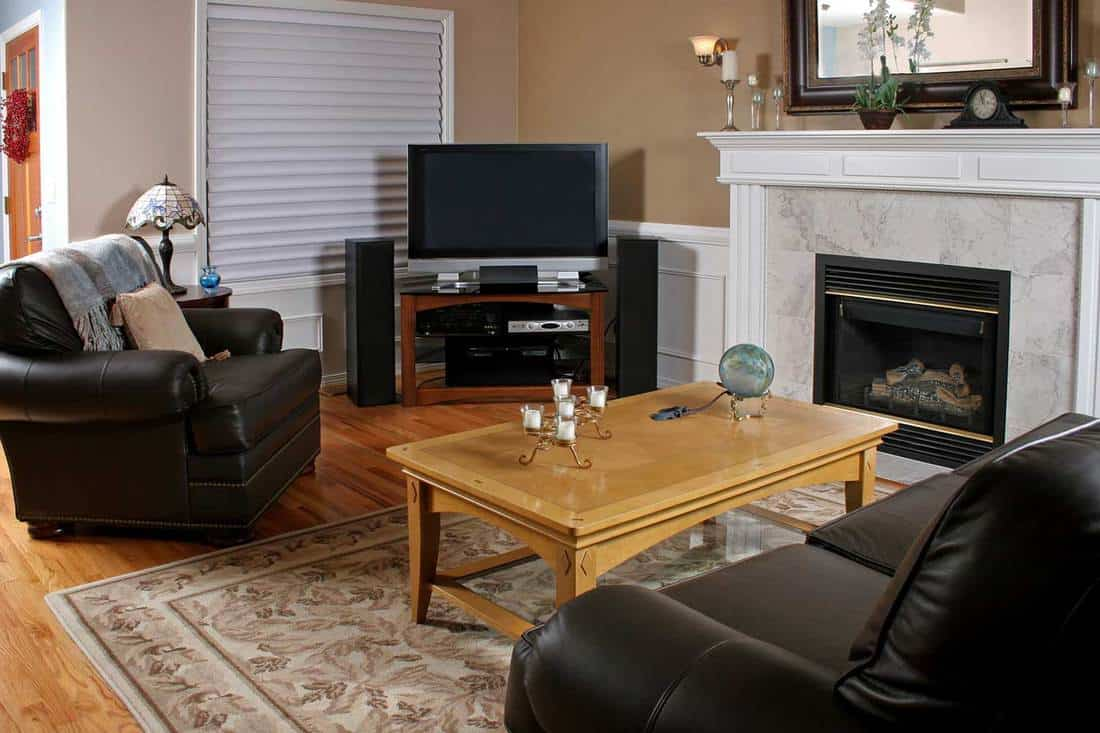 Modern family room with brown leather sofa, TV, fireplace and coffee table