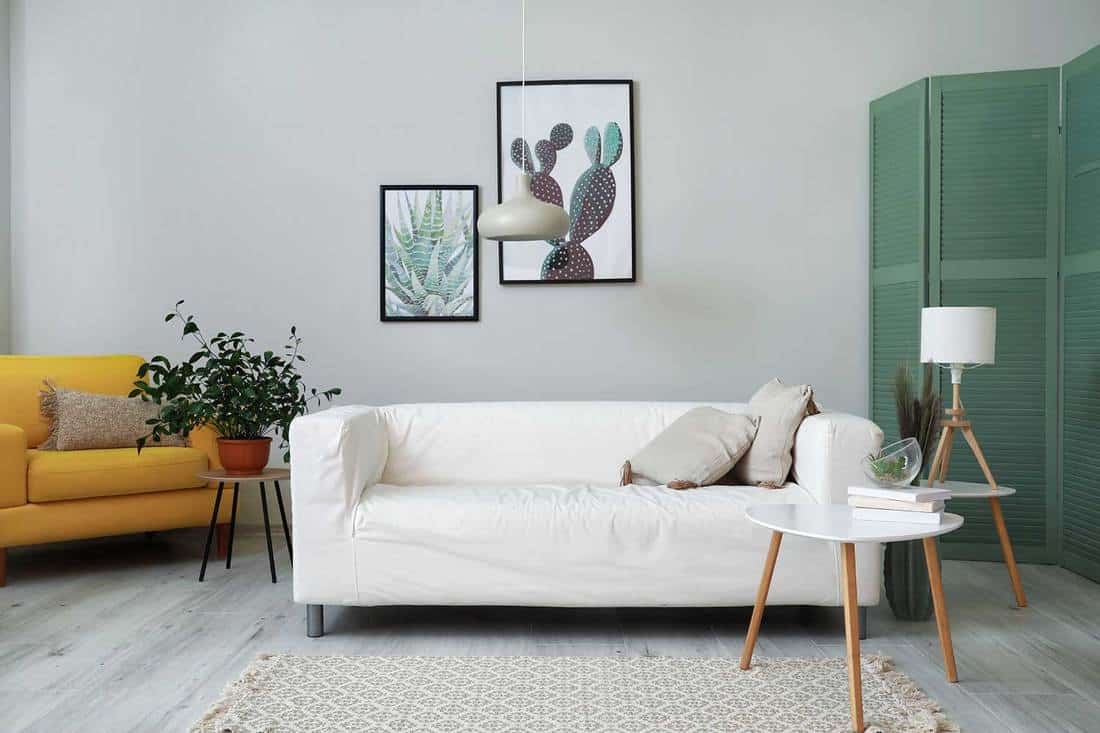 Modern light living room with white couch and parquet floor, couch cover stays in place