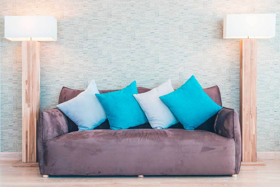 Modern living room with purple sagging couch in between standing lamps