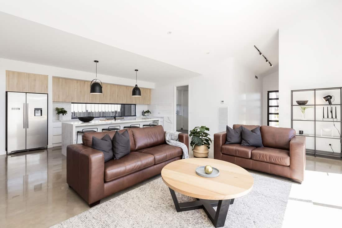 Open plan scandinavian styled family living room and kitchen with brown leather sofa