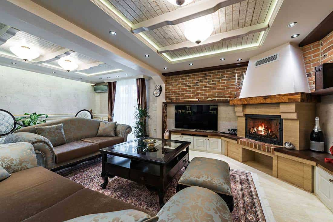 Spacious living room interior in a luxury apartment with cozy sofa, brick walls and fireplace