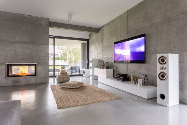 TV living room with large speakers window fireplace and concrete walls, 27 Living Rooms With A Fireplace And TV