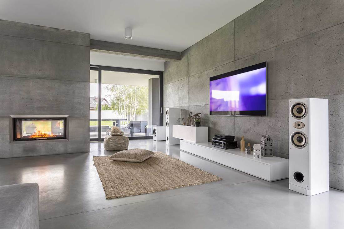 TV living room with large speakers, window, fireplace and concrete walls
