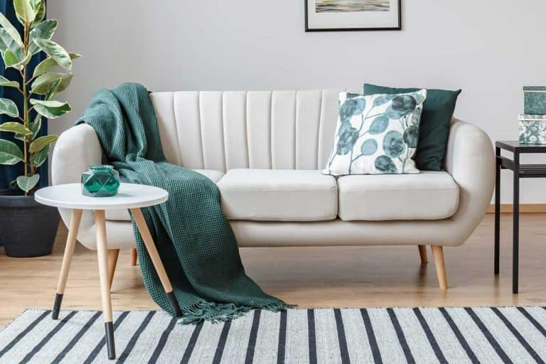 White couch with green blanket and throw pillows in cozy apartment living room, How to Keep Couch Cushions From Sliding