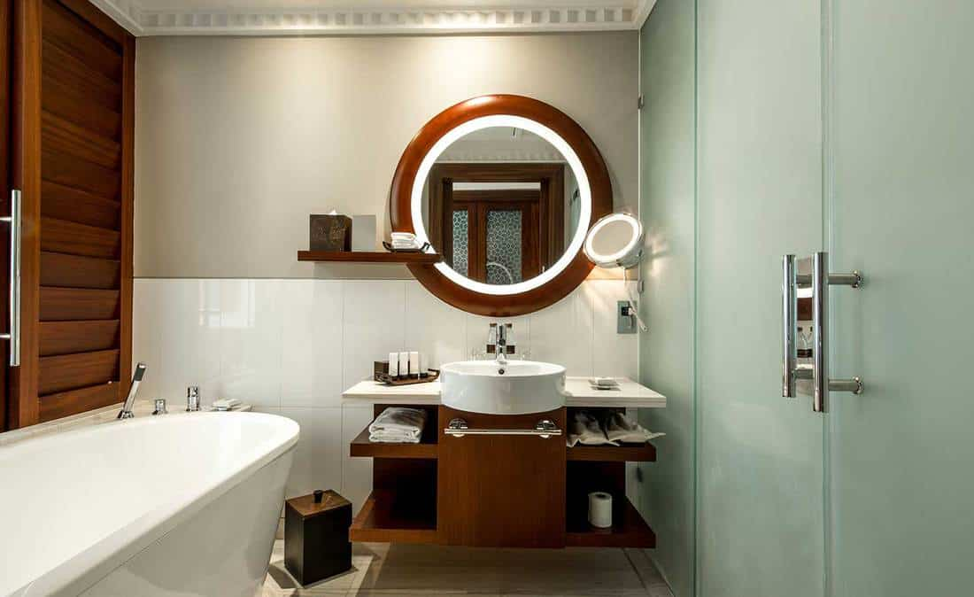 A modern bathroom suite with a nice large round mirror