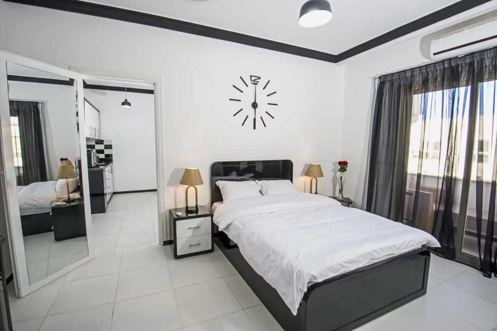 black and white modern bedroom with large floor mirror placed on the door