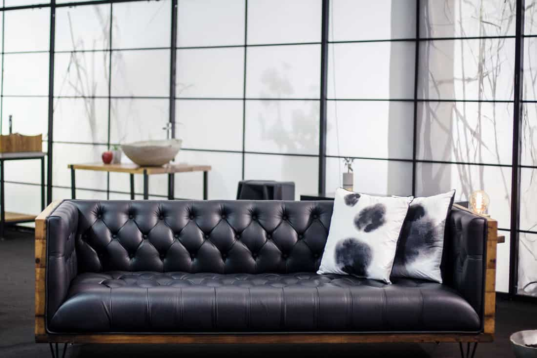 Black sofa with wooden framing and pillows placed on the right corner
