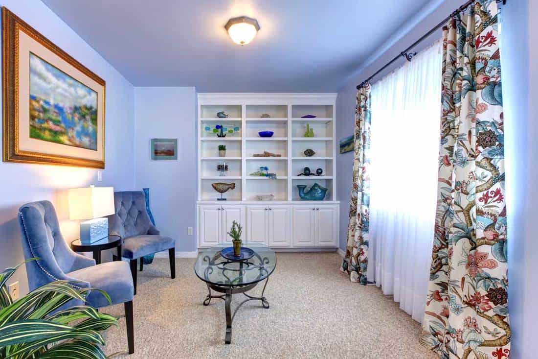 Blue room with two armchairs white cabinet and curtains