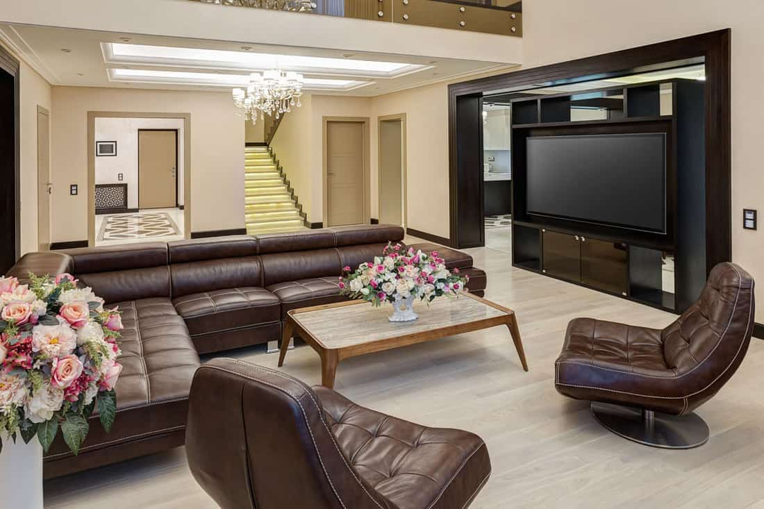 Brown couches with wooden table facing huge TV screen on living room