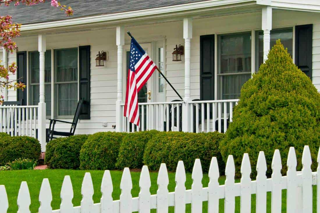 Colonial era house with hanging flag in the front porch