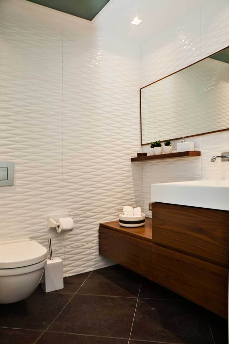 Contemporary bathroom design with large mirror, toilet and sink