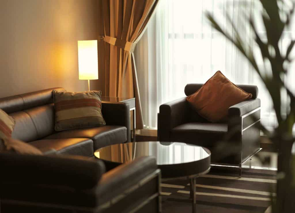 Contemporary living room with dark brown leather sofa , armchairs, coffee table and lit lamp - Luxurious hotel room