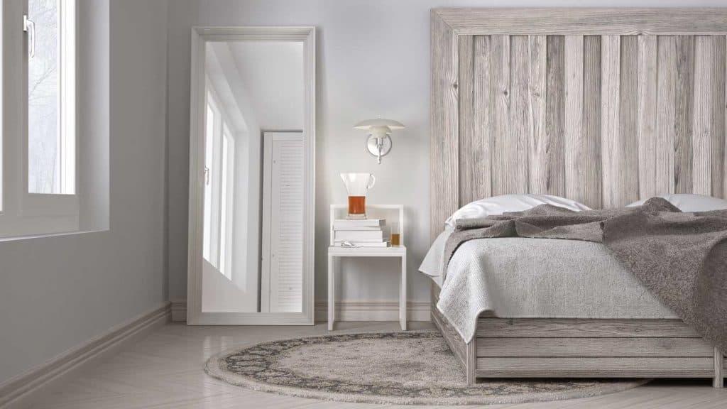 DIY bedroom with floor mirror beside the window, bed with wooden headboard